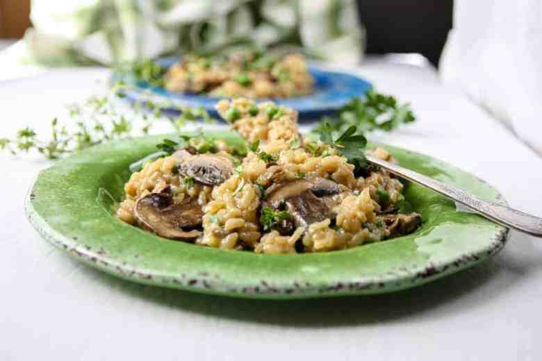 Two plates of mushroom risotto, a green plate in the forground, and a blue plate in the background