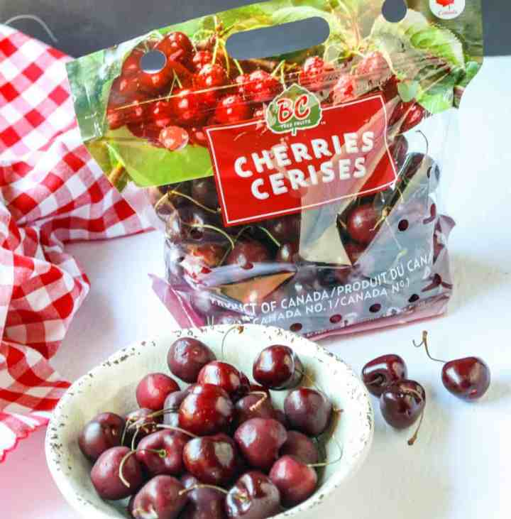 A package of cherries next to a bowl of cherries on a table