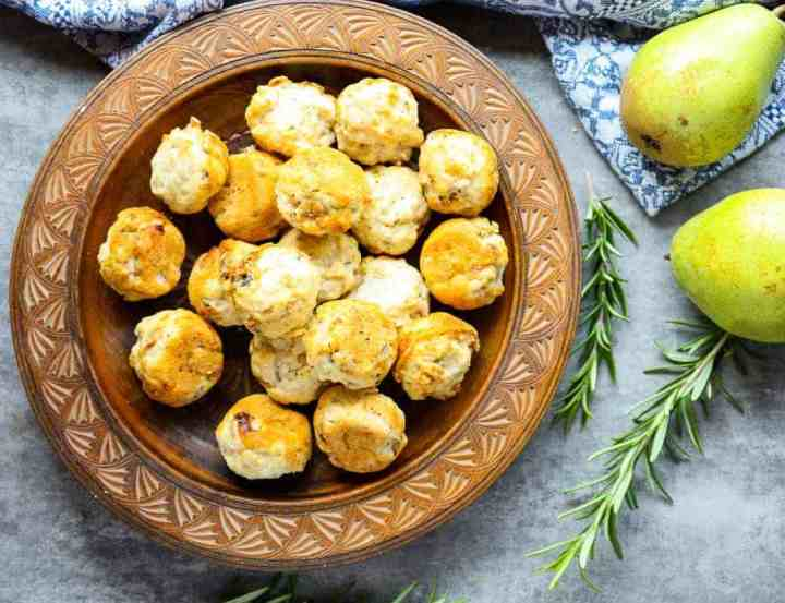 Wooden plate of pear & gorgonzola mini muffins beside two pears and sprigs of rosemary