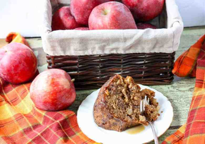 a slice of apple walnut spice cake on a white plate with a fork in front of a basket of apples