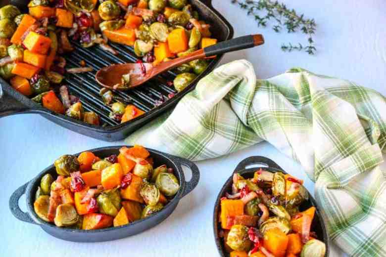 cast iron grill pan with roasted butternut squash, brussels sproups, cranberries & bacon, and two cast iron dishes of roasted vegetables