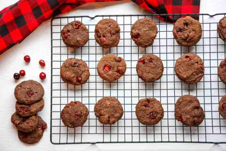 Double chocolate cranberry cookies cooling on a wire baking rack beside a black & red checkered kitchen towel