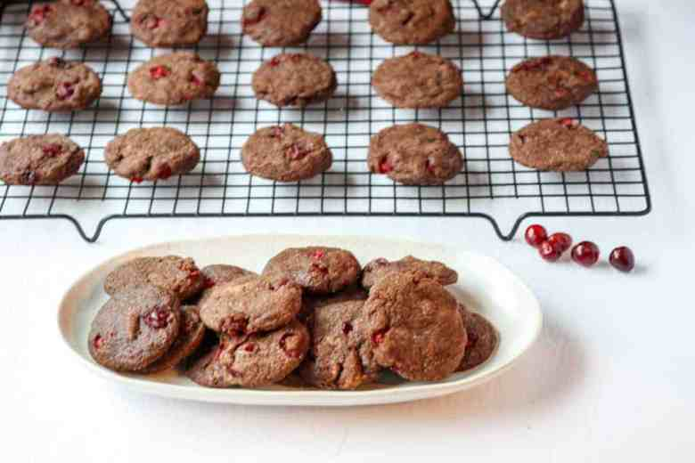 A white plate of chocolate cranberry cookies in front of cookies cooling on a wire rack