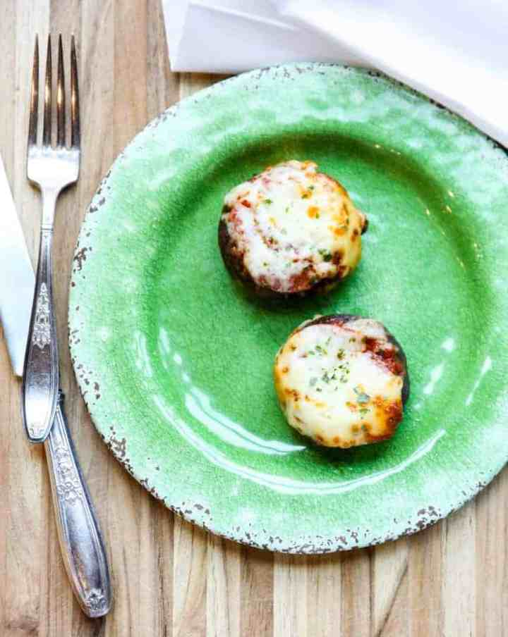 Two pizza stuffed mushrooms on a green plate