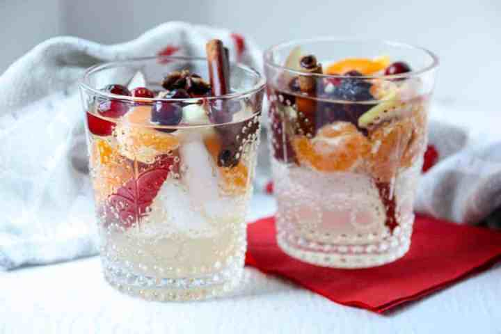 Two glasses of sangria filled with cinnamon sticks, apple slices, orange slices, and cranberries on awhite table with a red napkin.