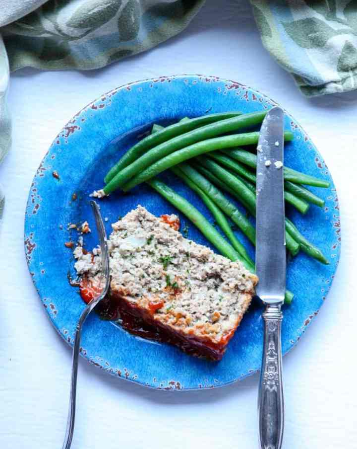 A piece of meatloaf  on a plate with a fork and knife