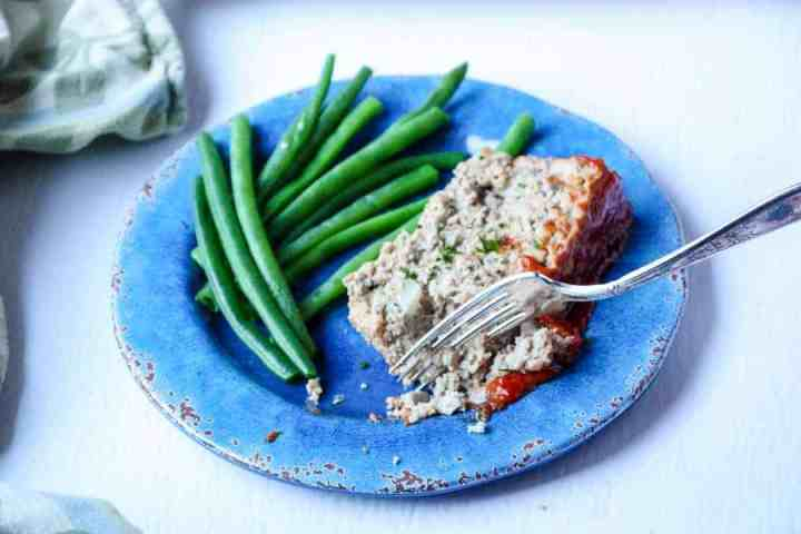 Meatloaf and green beans on a plate with a fork