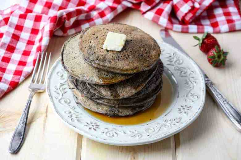 Stack of buckwheat pancakes on an embossed white plate with a pat of butter on top and maple syrup