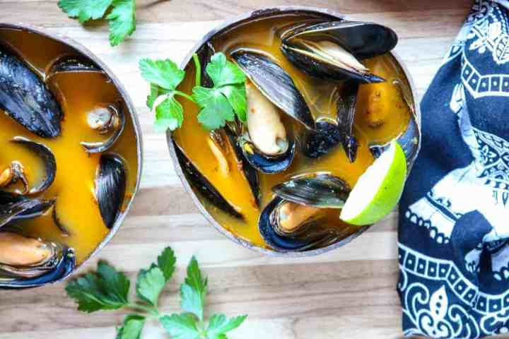 Mussels in orange broth in brown wooden bowl on wooden table