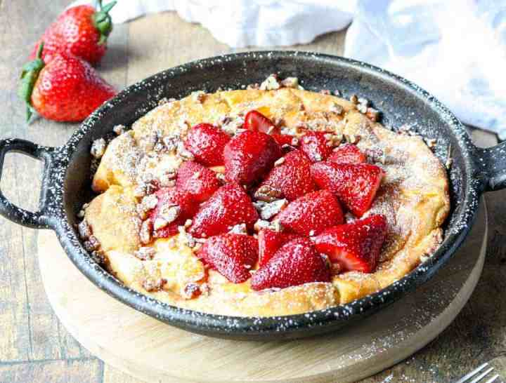 Top shot of strawberry Dutch baby gluten free in cast iron skillet.