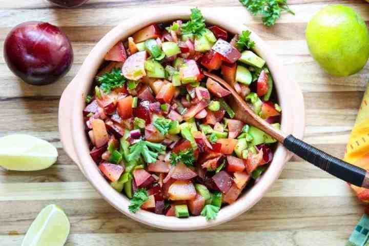 A bowl of fruit salsa with a wooden spoon