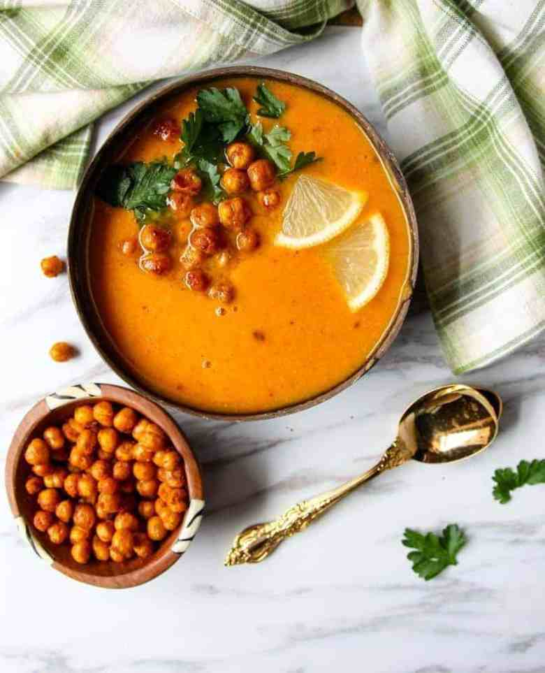 Bowl of sweet potato soup topped with lemon slices, roasted chickpeas, and parsley