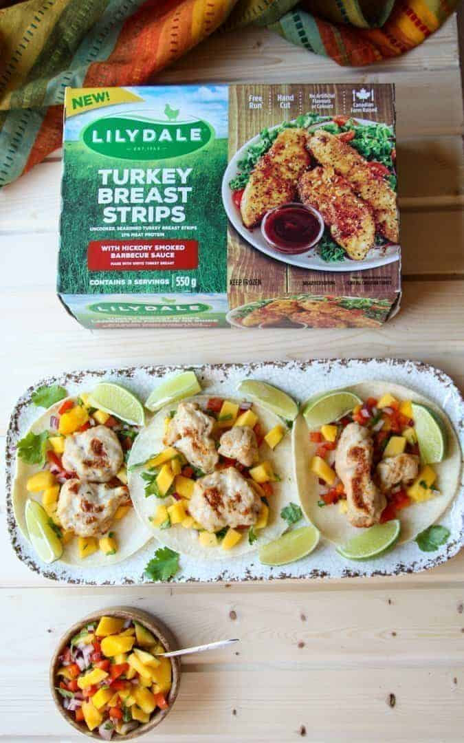 A platter of tacos on a table with a box of frozen turkey strips