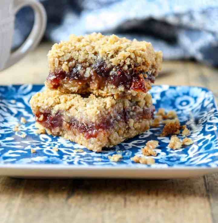Two cranberry date squares on a blue & white plate.
