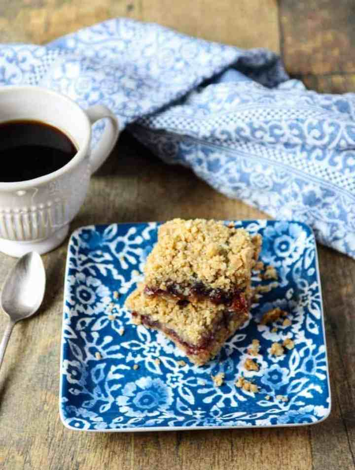 A cup of coffee on a table, with Cranberry and Date square
