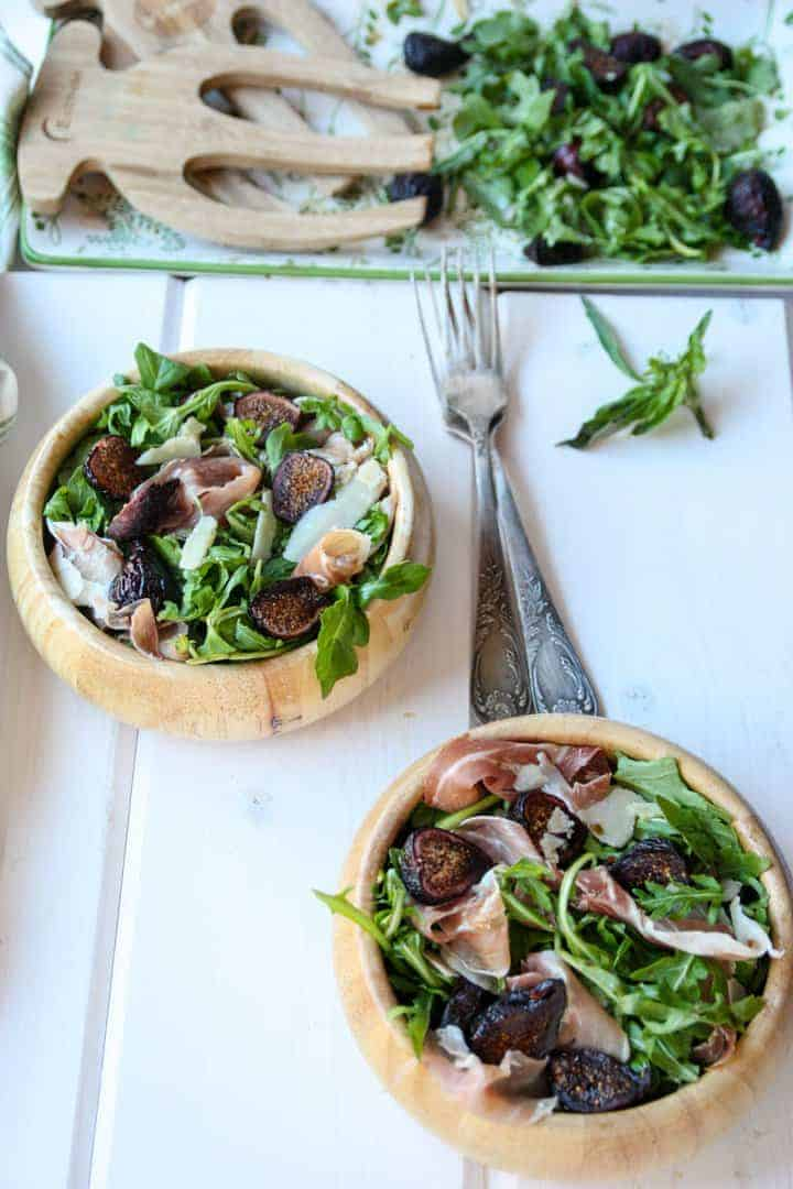 Two wooden bowls of salad with forks