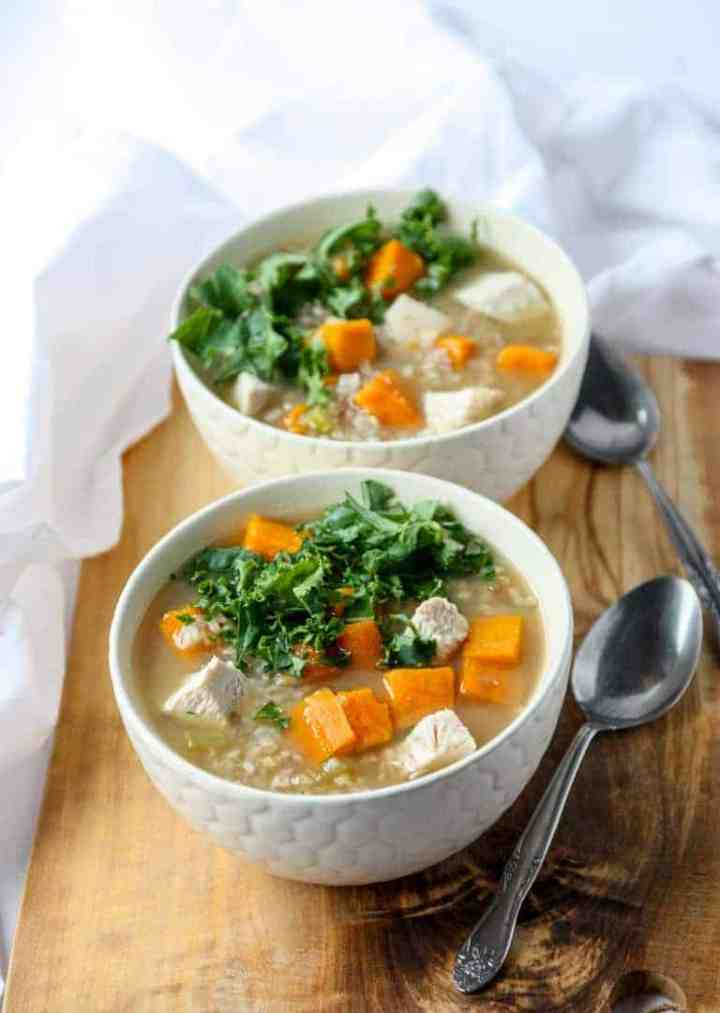 Two bowls of soup on a table with two spoons