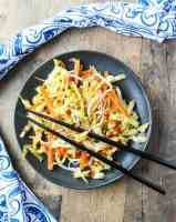 Top shot of vegetable stir fry on round black plate with two black chopsticks.