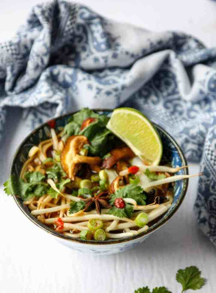 top shot of vegan pho in bowl with lemon wedge