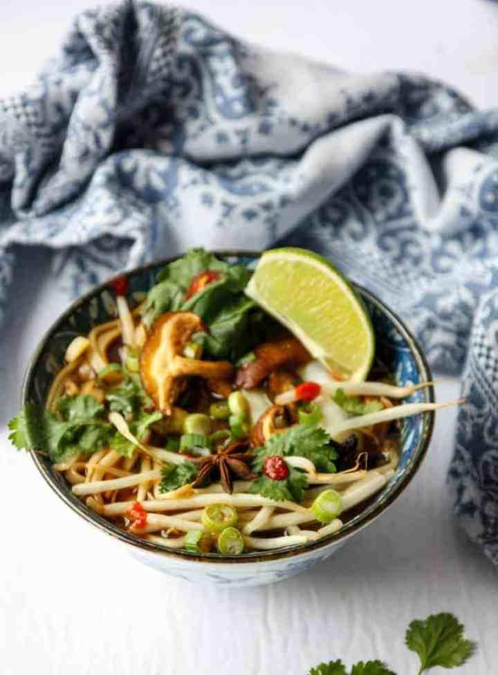 top shot of vegan pho in bowl with lemon wedge