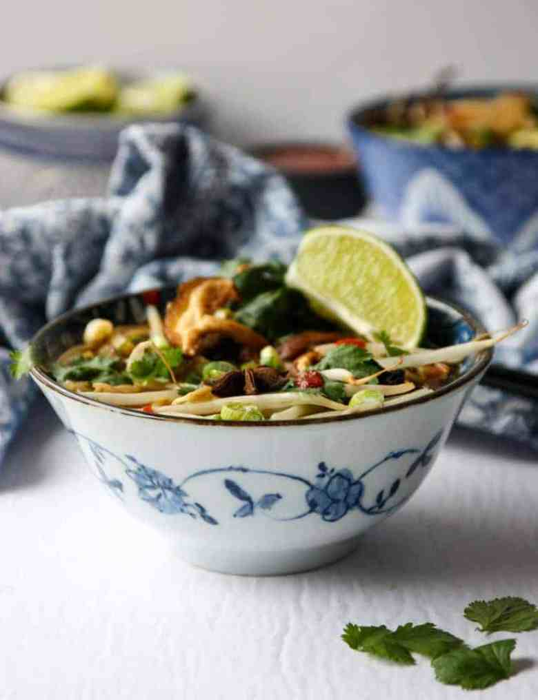blue & white asian style bowl of vegan pho soup with lime & cilantro