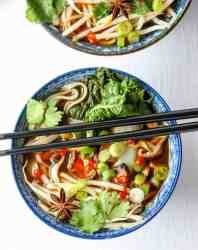 A bowl of vegetables and noodles with chopsticks