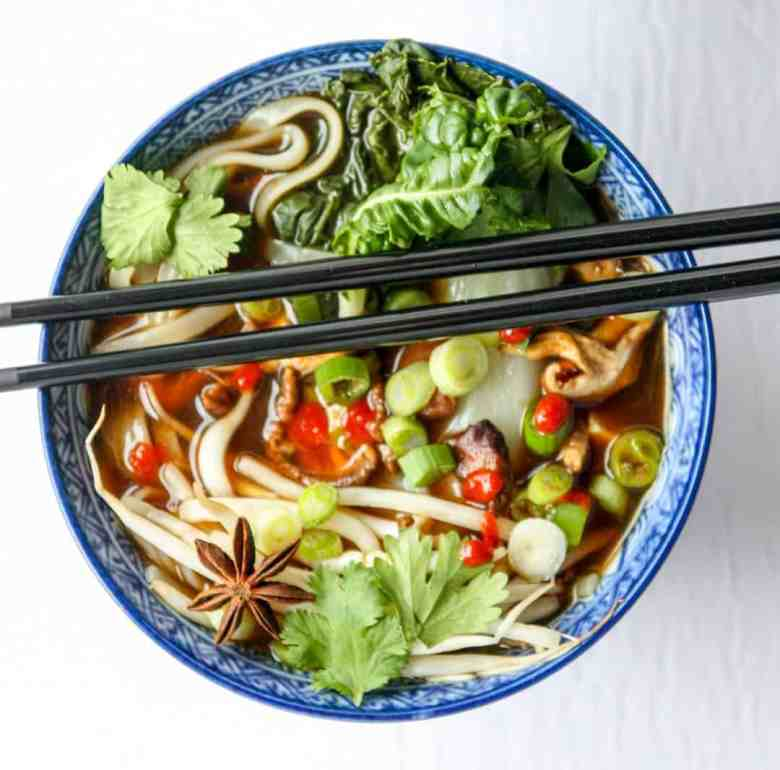 Blue bowl with vegan pho soup and two black chopsticks