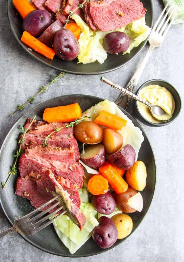 cooked and sliced slow cooker corned beef and cabbage with potatoes and carrots on two black plates with a dish of mustard