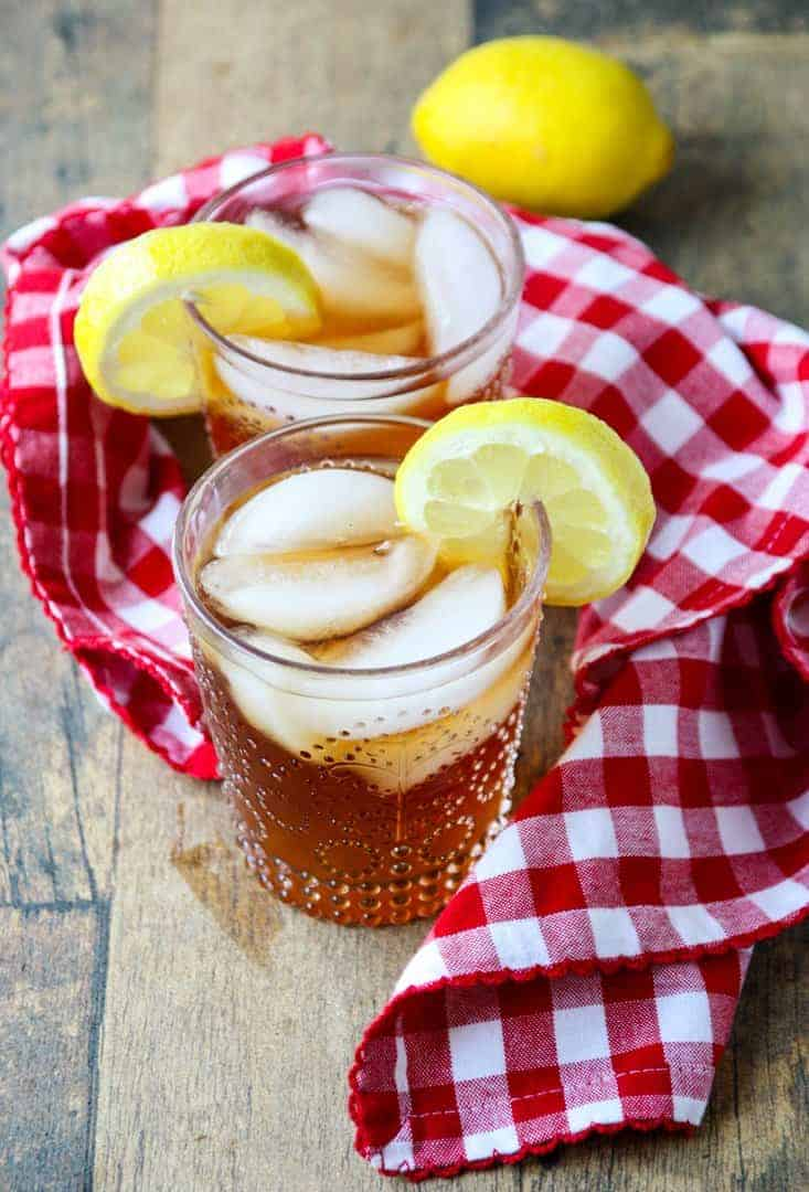 two glasses of spiked liced tea with ice cubes and lemon slices