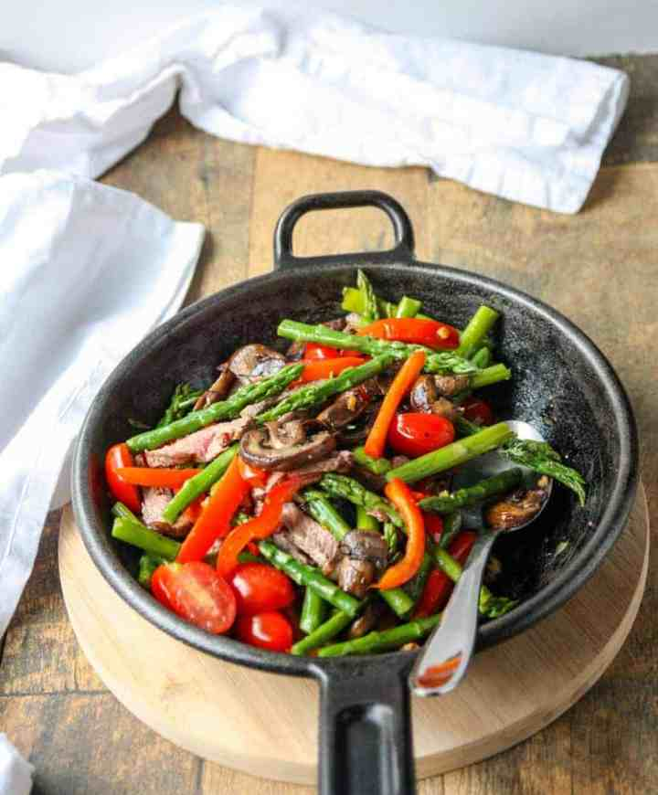 A cast-iron skillet with meat and vegetables