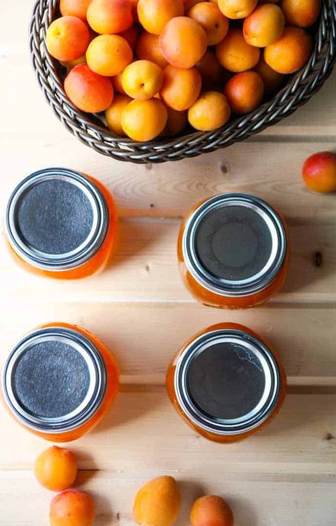 A bowl of apricots on a table, jars of jam