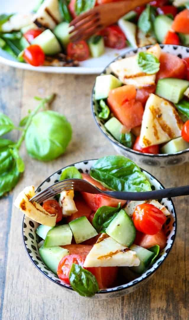 A bowl of fruit and vegetable salad, with Halloumi and Cucumber