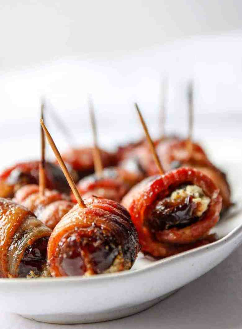 dates wrapped in bacon with toothpicks on a plate