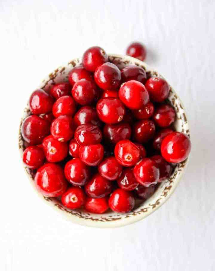 A bowl of cranberries on a table