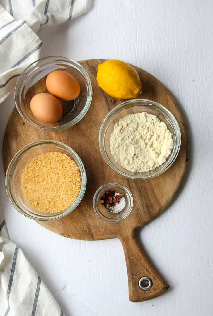 Bowls of bread crumbs, eggs, spices and a lemon on a wooden board