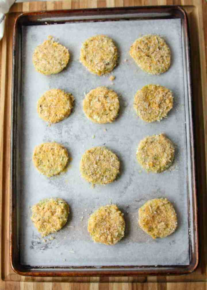 Breaded green tomato slices on a baking sheet