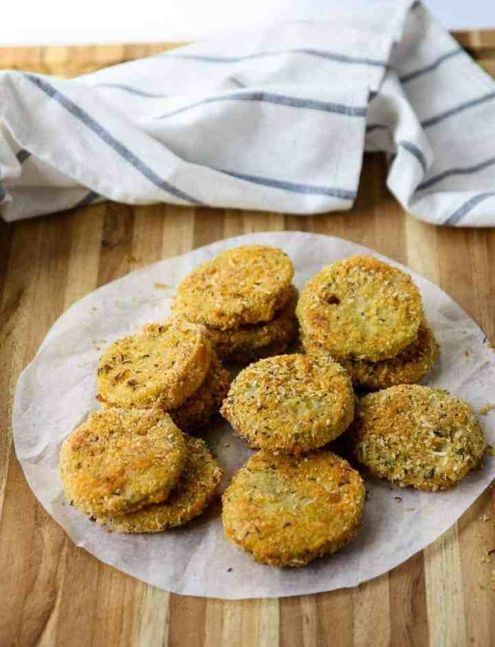 Fried green tomatoes on parchment paper on a wooden table