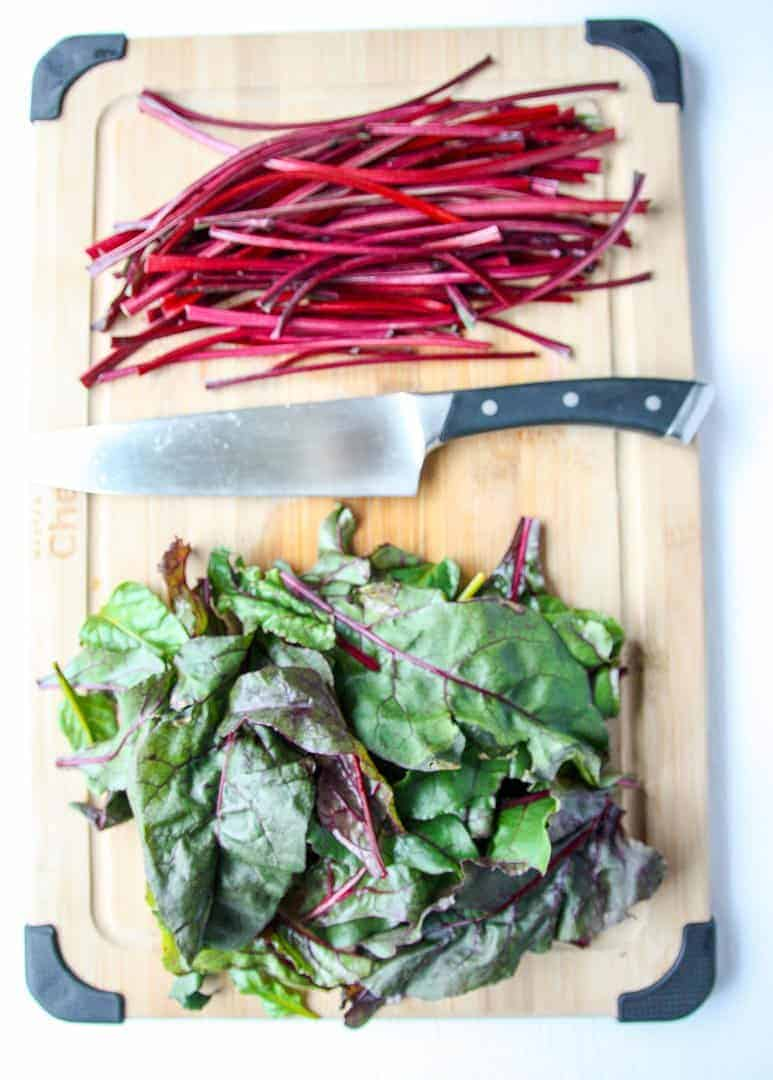 Beet leaves and stems on a wooden cutting board with a knife.