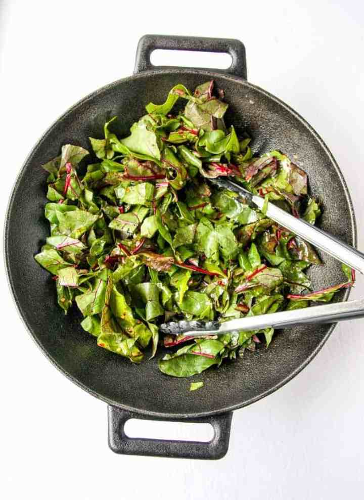 Beet Greens are sautéed in a pan with tongs.