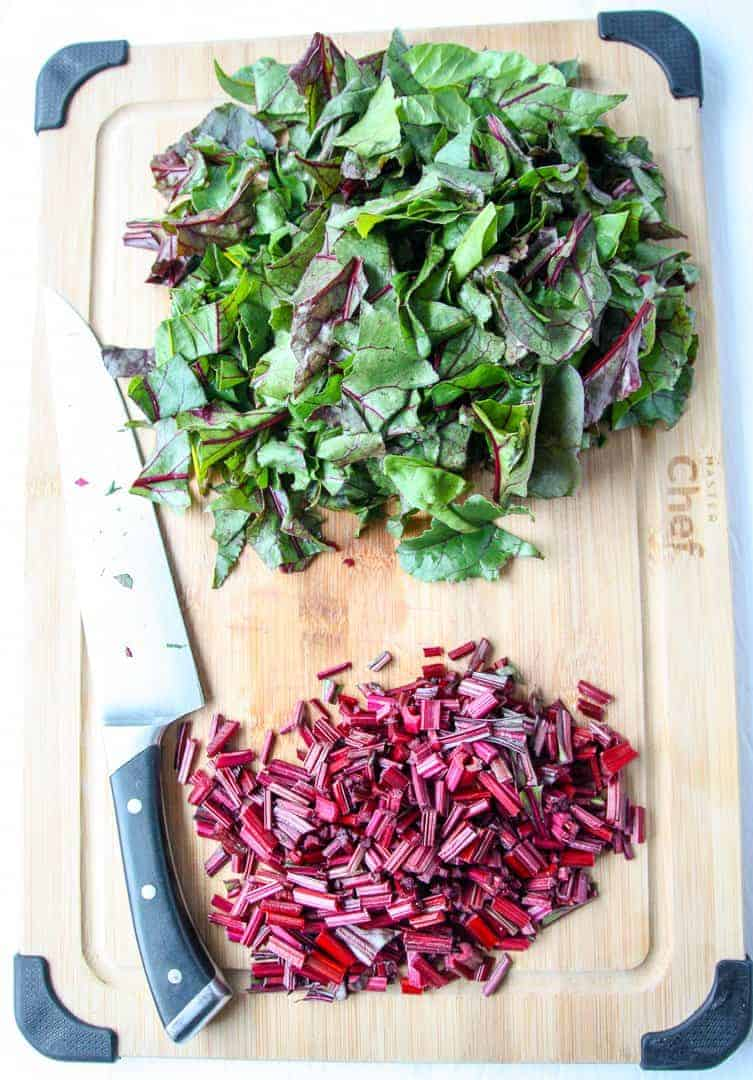 Chopped beet tops on a wooden cutting board with a knife.