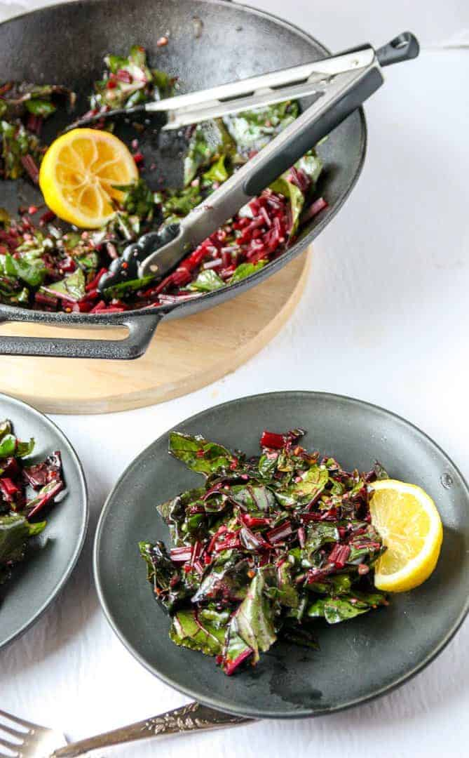Two plates of cooked beet tops with a lemon wedge