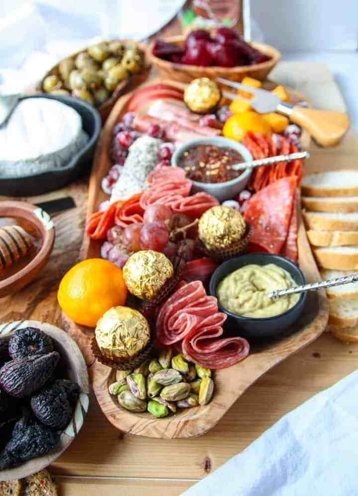 A wooden board full of sliced meats, cheeses, fruits and nuts, olives and chocolate.