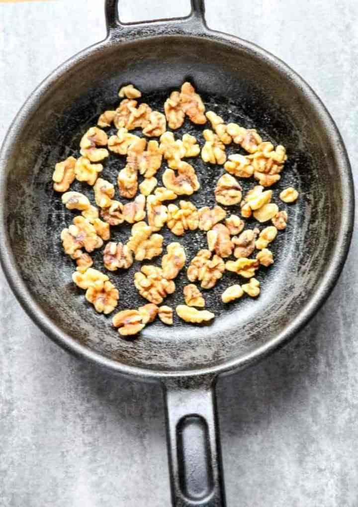 Walnuts are being toasted in a skillet on a stovetop