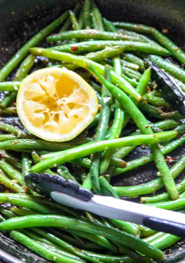 Close up of cooked string beans in a skillet.