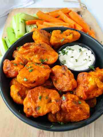 Gluten-free baked buffalo cauliflower bites on a black plate with carrot and celery sticks.