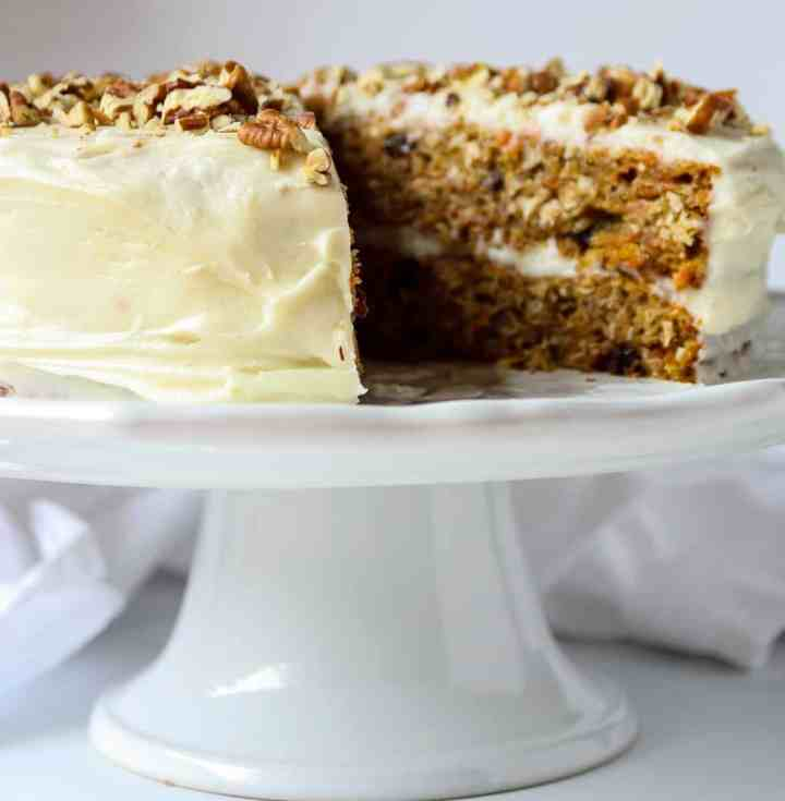 A carrot cake with cream cheese frosting on a cake stand with a slice removed.