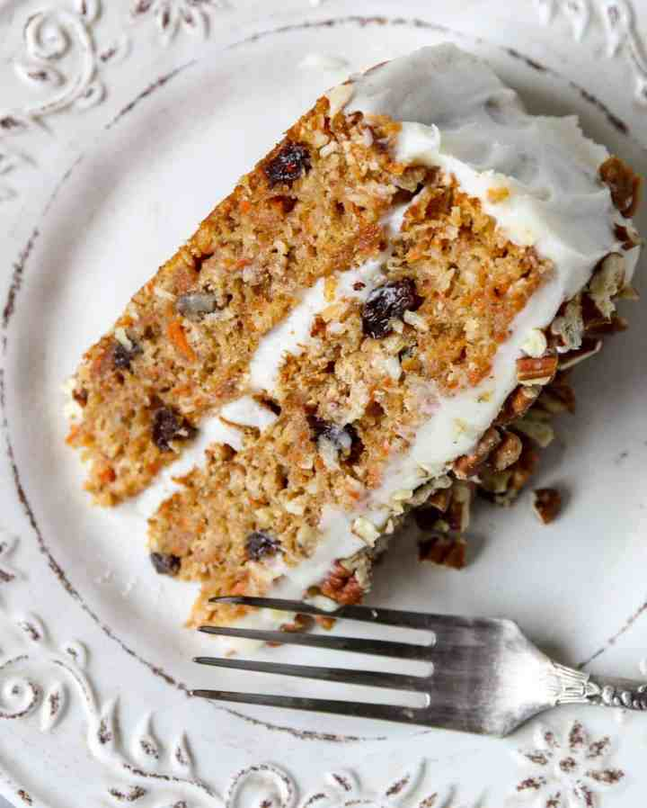 A slice of frosted carrot cake on a white plate with a silver fork.