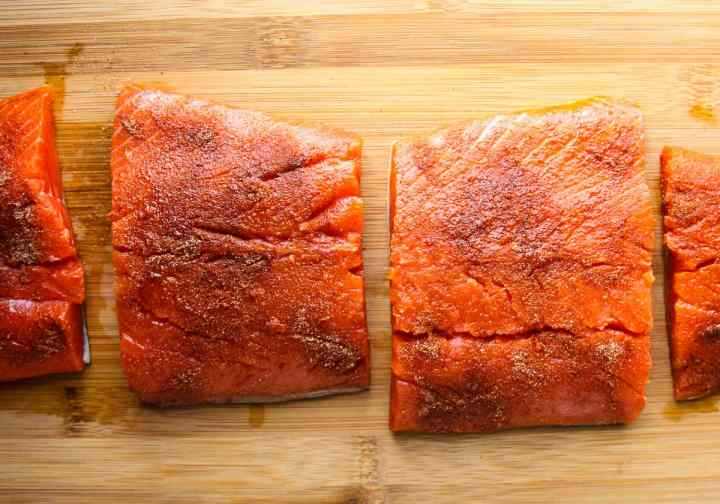 Salmon fillets being seasoned before cooking in the air fryer.