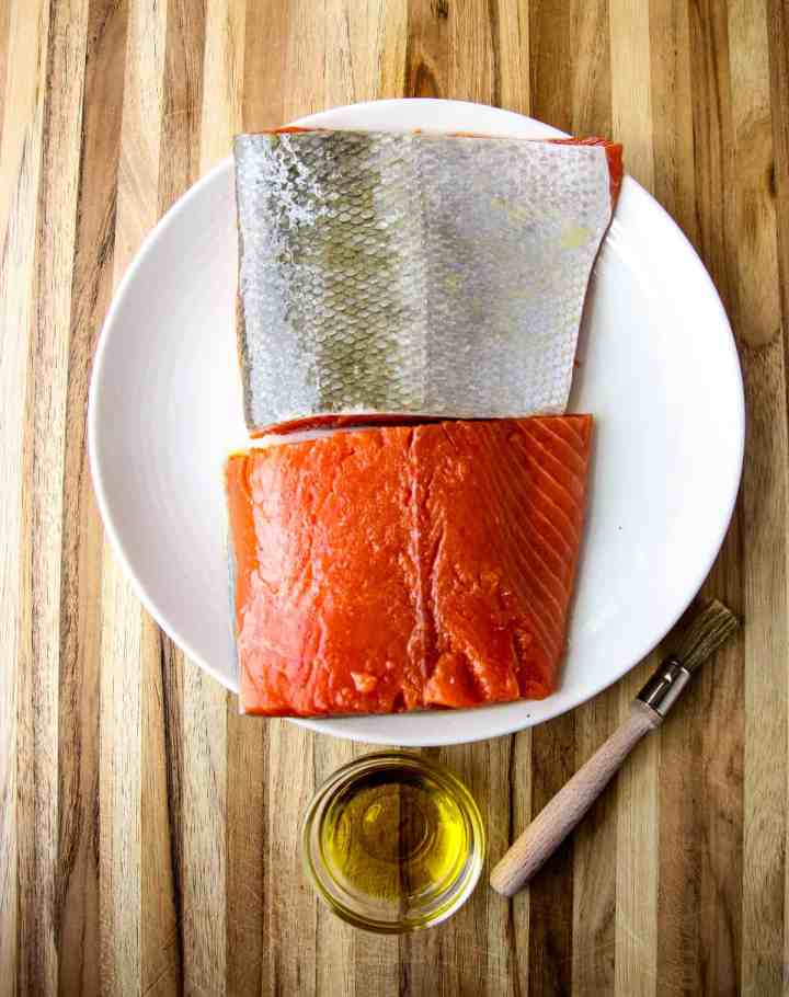 Salmon fillets being brushed with oil.