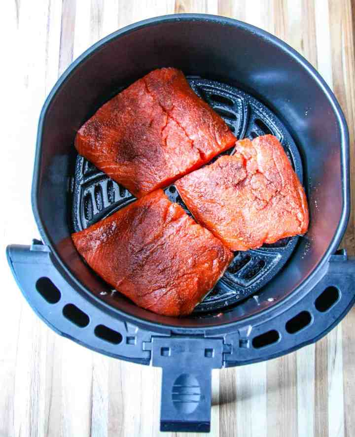 Three salmon fillets in an air fryer basket ready to be cooked.